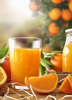 51575928 - glass of orange juice on a wooden table with bottle and orange sections. tree and field background with evening sun. vertical composition. front view