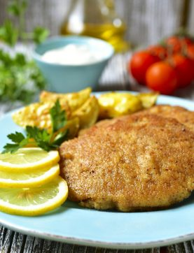 55103469 - viennese schnitzel on a blue plate on rustic background.